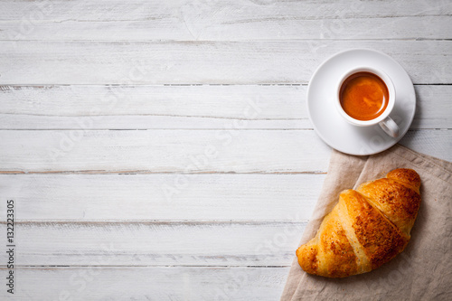 Fototapeta cup of espresso coffee with croissant on white wooden table, empty space on left obraz