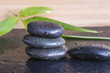 spa concept/massage stones and bamboo leaves on black slate background with water drops
