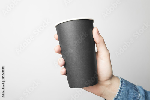 Fotobehang Cafe Hand in blue shirt is holding a black paper cup