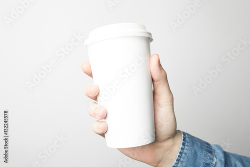 Foto op Plexiglas Cafe Hand in blue shirt is holding a white paper cup