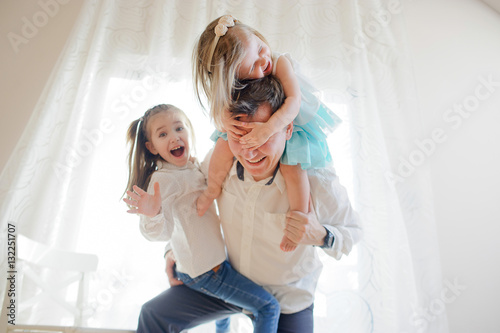 Fotografie, Obraz  Young father cheerfully spends time with the little daughters.