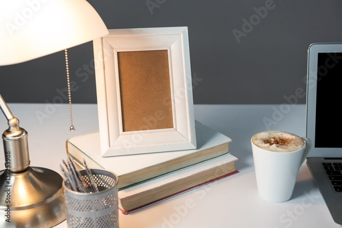 Fotografie, Obraz  Picture frame, cup of coffee with books and table lamp