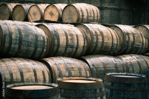 Leinwand Poster Whisky barrels full of whiskey in Scottish traditional distiller