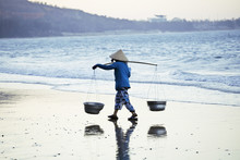 Vietnam Woman In Vietnamese Hat Walking On Seacost At Sunset