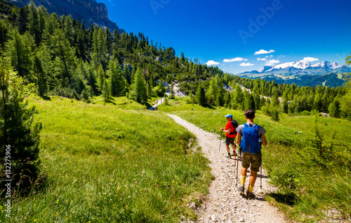 Obraz Pair of excursionist walking on mountainous trail. Summer Trekking - fototapety do salonu