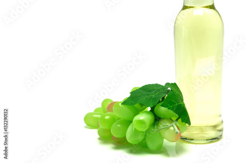 Poster Printemps Green grape and white wine bottle on white background.