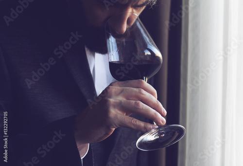 Fotografía  man tasting a glass of red wine