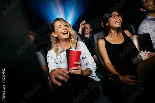 Laughing young people watching film in theater