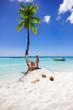 Girl sitting on the beach near palm tree