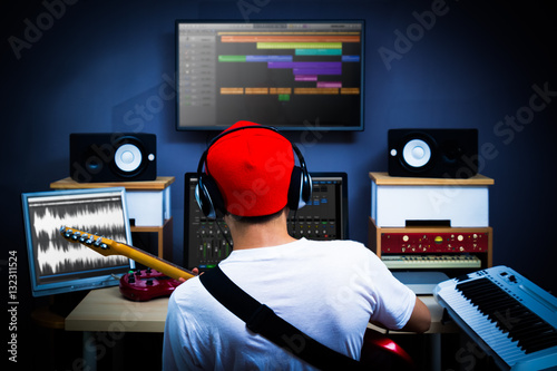 Fotografía  back of male musician playing guitar in recording studio for music background