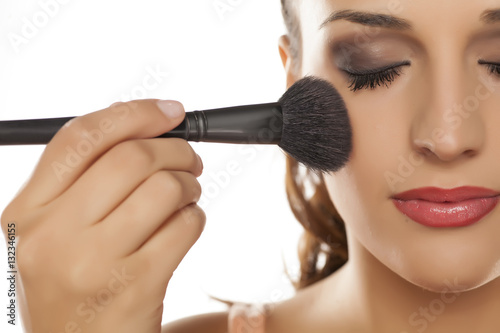Fotografía  young woman applied blush on her cheeks