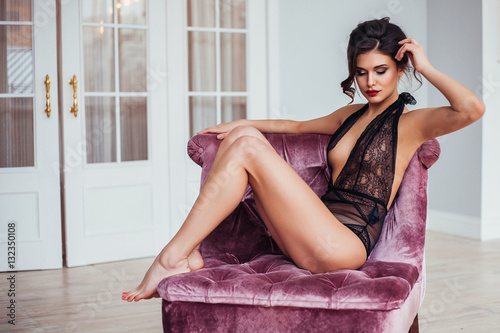 Young Beautiful sexy woman in seductive lingerie posing in bedroom Canvas Print