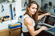 Sexy craftswoman working using a laptop in the garage