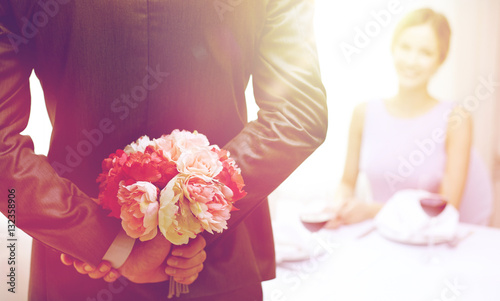 Photo  close up of man hiding flowers behind from woman