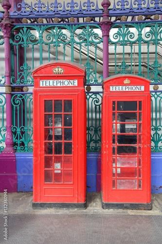 dwie-czerwone-londynskie-budki-telefoniczne-na-tle-zielonej-bramy