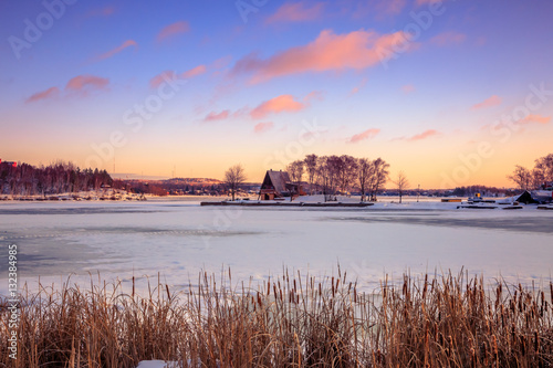 Obraz na plátně View of a frozen lake during sunrise in winter season