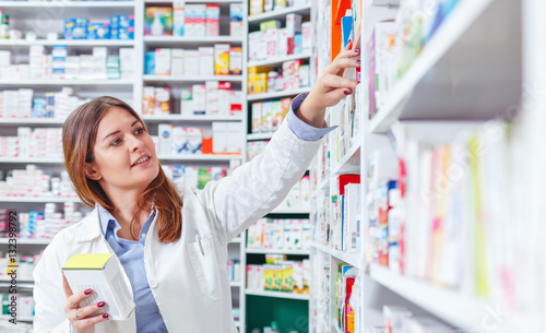 Photo sur Toile Pharmacie Photo of a professional pharmacist checking stock in an aisle of a local drugstore.