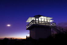Lit Fire Lookout At Night With Sunset And Moon In The Sky.