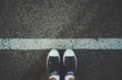 Leinwanddruck Bild - Male feet in white socks and gumshoes standing near grunge white line on gray asphalted road, ready to go