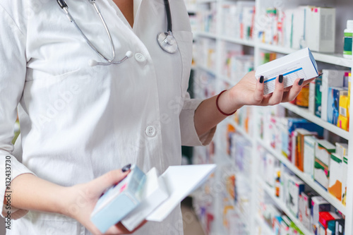 Woman pharmacist holding prescription checking medicine in pharmacy - drugstore.