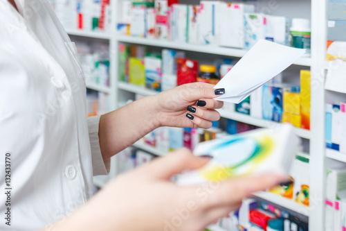Photo sur Toile Pharmacie Woman pharmacist holding prescription checking medicine in pharmacy - drugstore.