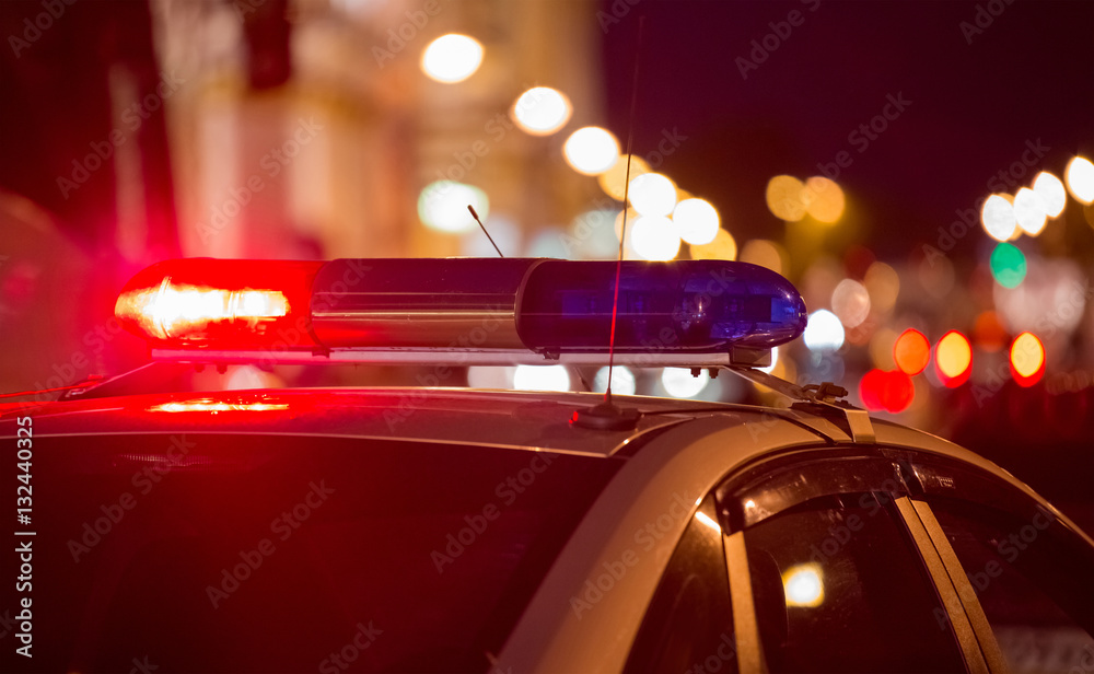 Fototapeta Red light flasher atop of a police car. City lights on the background