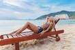 young slim blonde woman gets suntan on beach