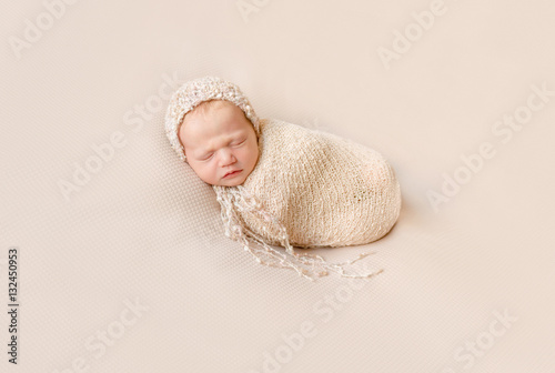 Fotografía  lovely wrapped baby in hat sleeping on a beige blanket