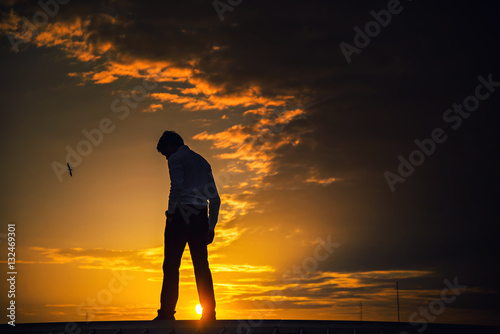 Fotografie, Obraz  Silhouette of a man standing with a sad look on after sunset.