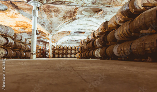 Fotografiet Old vintage whisky barrels filled of whiskey placed in order in