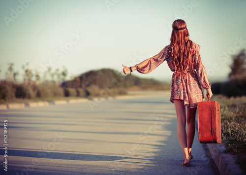 Young hippie woman hitchhiking on a road. Rear view Canvas Print