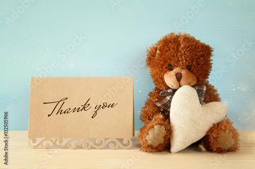 Cute teddy bear sitting and holding a heart