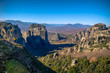 Man enjoys the breathtaking view of Meteora Roussanou Monastery a sunny winter day, Greece. Geological formations of big rocks with Monasteries on top of them.
