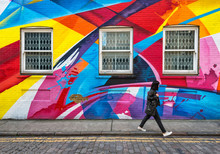 Shuttered Windows In Wall Covered In Rainbow Street Art