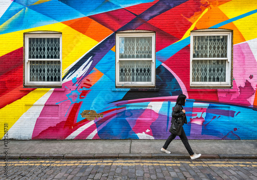 Foto auf AluDibond Graffiti shuttered windows in wall covered in rainbow street art