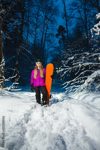 Tuinposter Wintersporten Young sexy woman with her snowboard in the dark winter forest