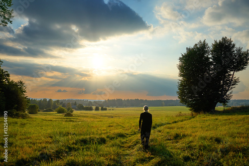 Valokuva  Man fascinated by the mystical glow of the sunset in a landscape