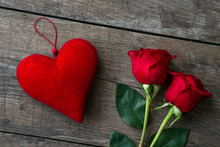 Red Roses And Red Heart On Wooden Table.