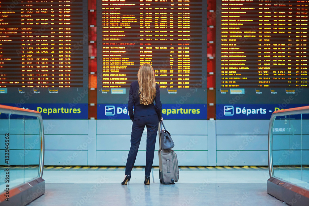 Fototapeta Woman with hand luggage in international airport terminal, looking at information board