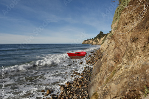 Red rowboat in the surf on a rocky beach beneath a cliff. Poster