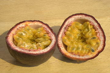 Cut open Passion Fruit or Maracuya, sunlit on wooden background