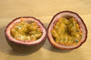 Cut open Passion Fruit or Maracuya, brightly lit on wooden background