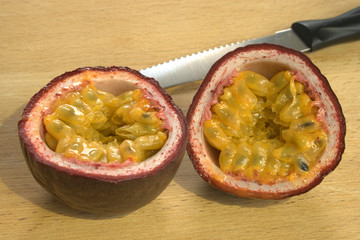 Cut open Passion Fruit or Maracuya, with knife, brightly lit on wooden background