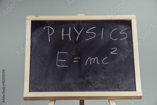 Photo  Physics word and formula E=mc2 on chalkboard