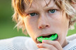Leinwandbild Motiv Boy putting in his mouth guard