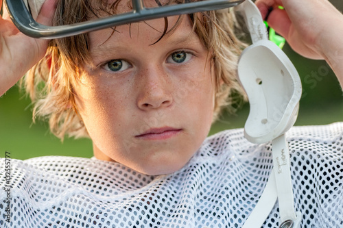 Young boy taking his football helmet off