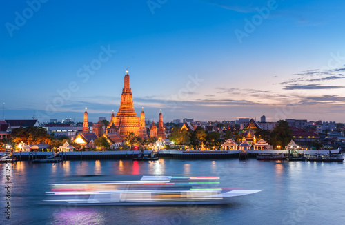 Photo  The boat was sailing in Chao Phraya River, background Wat Arun at sunset time ,Bangkok, Thailand