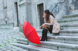 Pensive young woman with red umbrella sitting on the stairs in the old town.