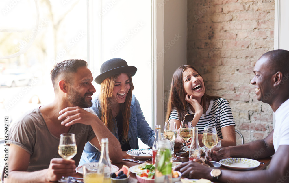 Fototapety, obrazy: Young friends having dinner and laughing together