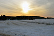 Winter landscape on countryside and sun shining through cloudy sky.